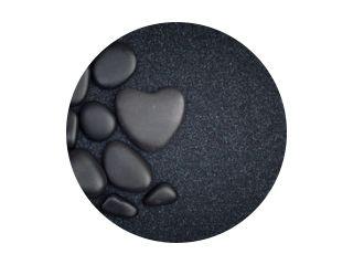 Black stones with black zen heart shaped rock on grain sand